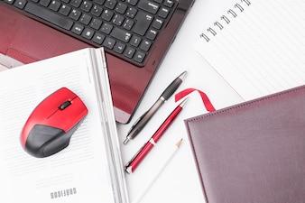 Bloc-notes et stylos près d'un ordinateur portable et d'une souris