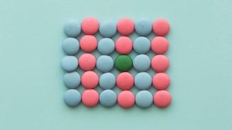 Bonbons verts disposés dans les bonbons roses et bleus sur fond coloré