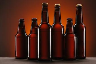 Bouchent la vue des bouteilles disposées de bière sur toile de fond orange