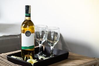 Bouteilles de vin et verres de vin sur plateau.