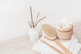 Brosse; serviette et cotons-tiges sur une surface en bois
