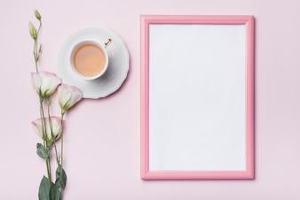 Cadre photo blanc avec bordure rose; tasse de thé et de fleurs fraîches d'eustoma sur fond coloré