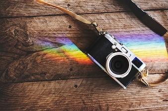 Caméra sur table en bois avec reflet de lumières prismatiques