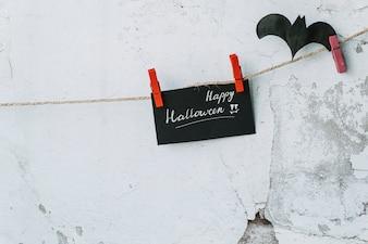 Carte noire avec une inscription heureuse d'Halloween et une chauve-souris