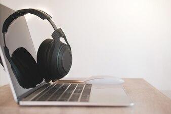 Casque noir, smartphone et ordinateur portable sur le bureau.
