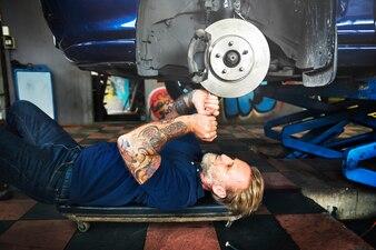 Caucasien auto mécanicien homme couché reparer le frein à disque de voiture dans le garage