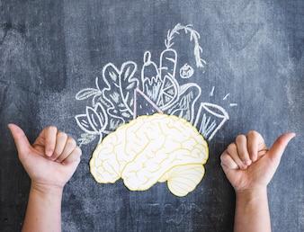Cerveau et légumes dessinés avec le pouce en haut signe sur le tableau noir