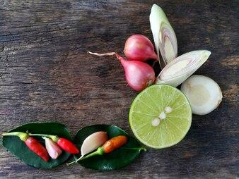 Citron vert à l'ail et à la citronnelle, échalote, piment et feuille sont sur planche de bois