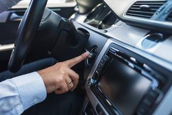 Close-up d'un homme en insérant la clé pour démarrer la voiture