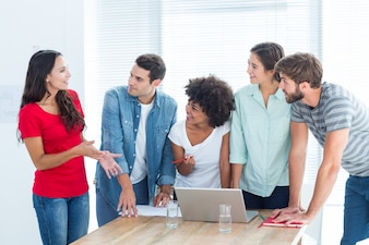 Collègues réunis autour d'un ordinateur portable au bureau