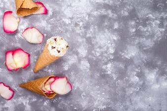 Composition de gaufres à la crème glacée avec des pétales de roses sur fond de pierre
