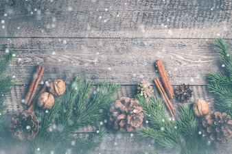 Composition de Noël fond. Bâtons de cannelle, pommes de pin, branches de sapin sur dos en bois