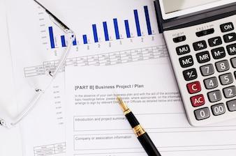 Concept d'affaires avec stylo plume et lunettes et calculatrice sur le plan d'affaires