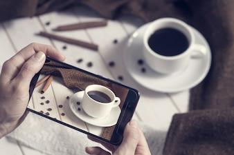 Concept de l'atelier de blogging nourriture photographie Instagram. Une photos de la main de la tasse de café sur