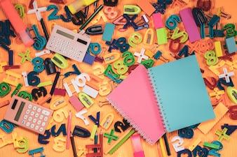 Concept de retour à l'école. Ordinateur portable et matériel éducatif sur fond orange.