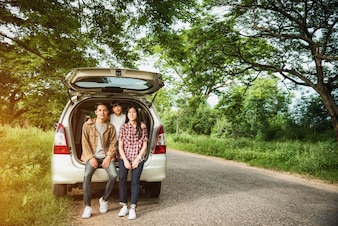Conduire dans la famille de vacances; famille asiatique sont heureux assis dans le coffre ouvert d'une voiture