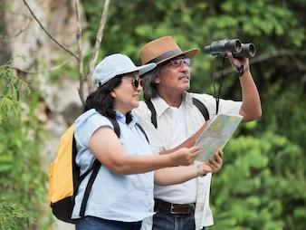 Couple de personnes âgées voyagent en vacances d'été. ils se tiennent la main et font de la randonnée ensemble.