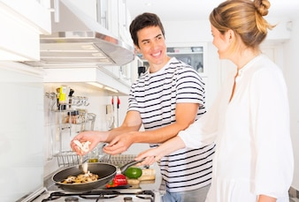 Couple heureux, debout, cuisine, préparation, champignons, poêle