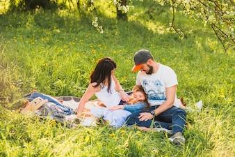 Couple regardant la fille assise sur l'herbe verte dans le parc