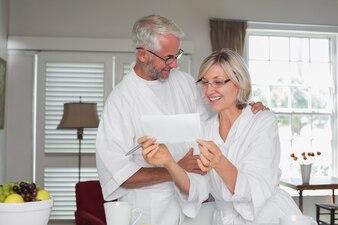 Couple senior en regardant un document à la maison
