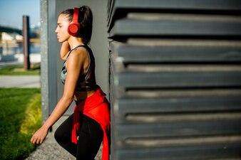 Coureur féminin attrayant prenant une pause après avoir fait du jogging à l'extérieur
