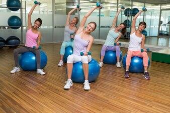 Cours de conditionnement physique tenant des haltères sur des balles d'exercice en studio