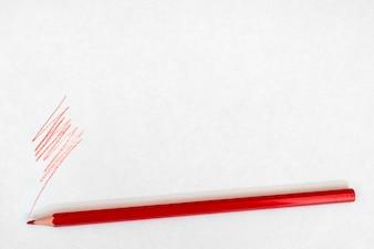 Crayon rouge écrit sur du papier blanc.