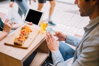 Crop couple avec des gadgets dans le café de la rue