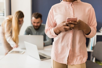 Crop femme à l'aide de smartphone au bureau