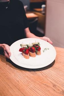 Crop serveuse mettant plaque avec des tartines sur la table