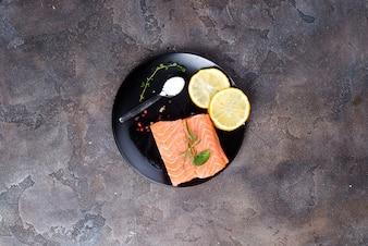 Darnes de saumon sur glace au citron et sel sur plaque noire. Protéines maigres.