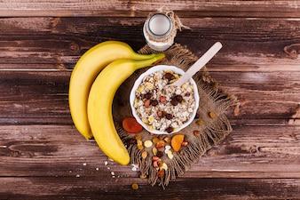 Délicieux petit-déjeuner sain fait de lait et de porridge avec des noix, des pommes et des bananes