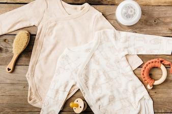 Deux bébés onesie; brosse; bouteille de lait; jouet et sucette sur table en bois