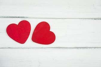 Deux coeurs rouges sur un fond en bois blanc, concept de l'amour.