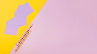 Deux crayons; papier cartonné et notes adhésives sur fond coloré