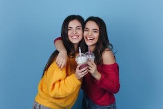 Deux filles se tiennent côte à côte et sourient pendant qu'elles boivent un milk-shake et un cocktail