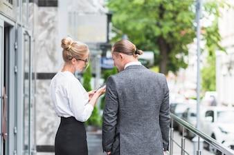 Deux, gens affaires, regarder smartphone
