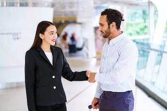 Deux hommes d'affaires serrant la main à un partenaire.