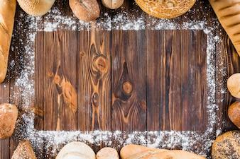 Différents types de pain répartis au bord de la farine sur une table en bois