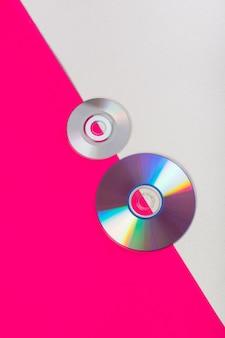 Disques compacts sur un double fond rose et blanc