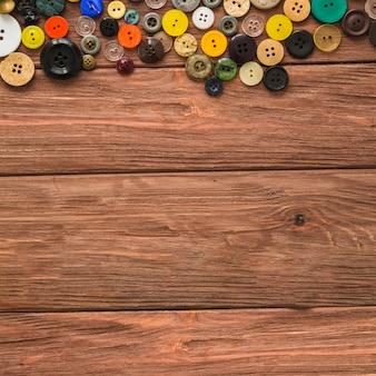 Divers boutons colorés sur une planche de bois