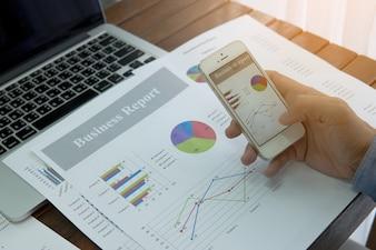 Documents d'affaires sur la table de bureau avec téléphone intelligent et graphique financier