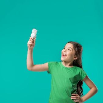 Douce fille debout avec lampe en studio