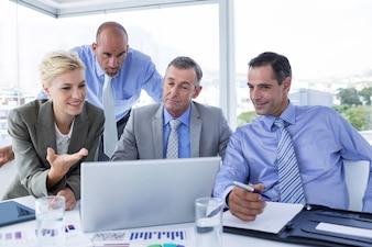 Équipe commerciale travaillant ensemble sur ordinateur portable