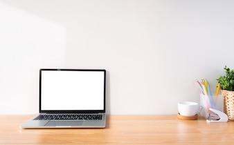 Espace de travail et ordinateur portable à écran blanc.