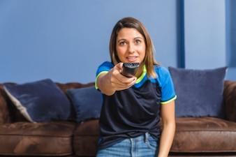 Fan de football féminin avec télécommande sur canapé