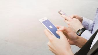 Femme à l'aide de l'application facebook sur mobile près de l'homme portant une montre intelligente