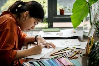 Femme asiatique travaille sur sa main dessinant des illustrations
