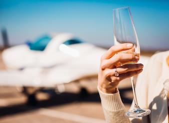 Femme avec une bague de mariage tient le verre de champagne debout dans l'aéroport