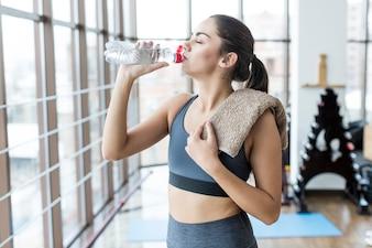 Femme avec une serviette potable dans la salle de gym